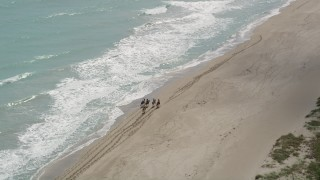AX0033_028 - 5K stock footage aerial video of orbiting horseback riders on the beach and blue ocean waters, Florida