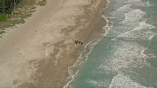 AX0033_030 - 5K stock footage aerial video of orbiting away from horseback riders on the beach, Fort Pierce, Florida