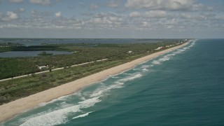 AX0033_067 - 5K stock footage aerial video of following the beach and blue waters on the coast, Melbourne Beach, Florida