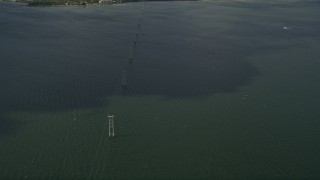 AX0033_072 - 5K stock footage aerial video of orbiting power lines crossing a river, Melbourne Beach, Florida