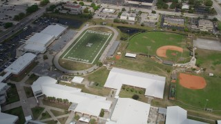 AX0033_079 - 5K stock footage aerial video fly over a high school toward the football field, Melbourne, Florida