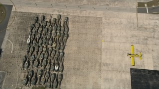 AX0033_081 - 5K stock footage aerial video of tilting to helicopter bodies stored at Melbourne Regional Airport, Florida