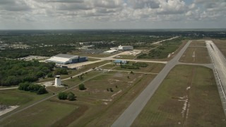 AX0033_082 - 5K stock footage aerial video flyby a runway and hangar at Melbourne Regional Airport, Florida