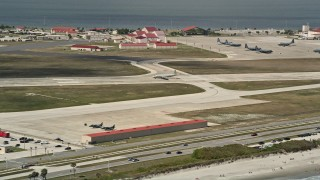 AX0034_003 - 5K stock footage aerial video of flying by a military plane on the runway, Patrick Air Force Base, Florida