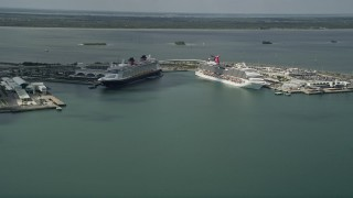AX0034_017 - 5K stock footage aerial video of approaching Carnival and Disney Cruise Ships, Port Canaveral, Florida