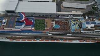 AX0034_019 - 5K stock footage aerial video approach and tilt to a docked Carnival Cruise Ship, Port Canaveral, Florida