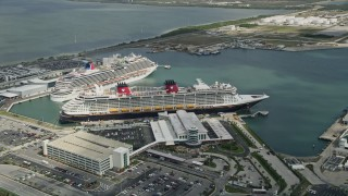 AX0034_020 - 5K stock footage aerial video orbit Disney and Carnival Cruise Ships, Port Canaveral, Florida