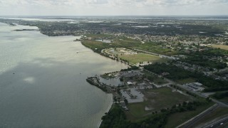 AX0034_024 - 5K stock footage aerial video of flying by a community park along the river, Merritt Island, Florida