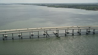 AX0034_025 - 5K stock footage aerial video of orbiting a causeway, Merritt Island, Florida