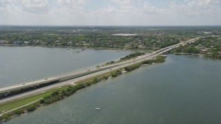 AX0034_026 - 5K stock footage aerial video of panning across a causeway revealing residential neighborhoods, Cocoa, Florida