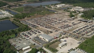 AX0034_030 - 5K stock footage aerial video of approaching an auto salvage lot, Cocoa, Florida