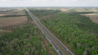 AX0034_064 - 5K stock footage aerial video of following an Expressway through trees and a rural area, La Belle, Florida
