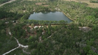 AX0034_066 - 5K stock footage aerial video of approaching a small lake and campground among trees, La Belle, Florida