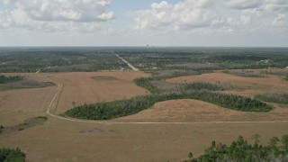 AX0034_069 - 5K aerial stock footage video fly over marshland toward town, Wedgefield, Florida