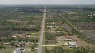 AX0034_070 - 5K stock footage aerial video of flying over homes and trees in Wedgefield, Florida