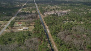 AX0034_071 - 5K stock footage aerial video of following a canal past homes and trees, Wedgefield, Florida