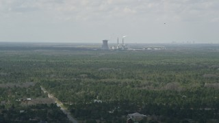 AX0034_072 - 5K stock footage aerial video fly over trees toward a coal fired power generation facility, Orlando, Florida