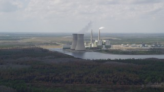AX0034_076 - 5K stock footage aerial video approach to a a coal fired power generation facility, Orlando, Florida