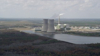 AX0034_077 - 5K stock footage aerial video of flying by a coal fired power generation facility, Orlando, Florida