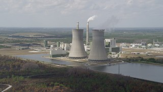 AX0034_078 - 5K stock footage aerial video of flying by a coal fired power generation facility, Orlando, Florida