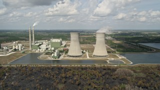 AX0034_080 - 5K stock footage aerial video of flying by a coal fired power generation facility, Orlando, Florida