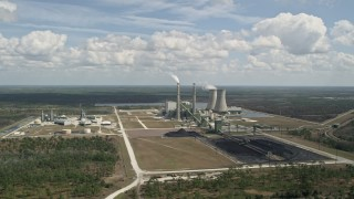 AX0034_082 - 5K stock footage aerial video fly away from a coal fired power generation facility, Orlando, Florida