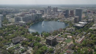 AX0034_086 - 5K stock footage aerial video tilt from residential neighborhoods revealing Lake Eoloa and Downtown Orlando, Florida