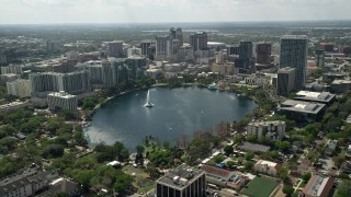 AX0034_086E - 5K stock footage aerial video tilt from residential neighborhoods revealing Lake Eoloa and Downtown Orlando, Florida