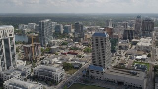 AX0034_100 - 5K stock footage aerial video of flying over Downtown Orlando office buildings toward high-rises, Florida