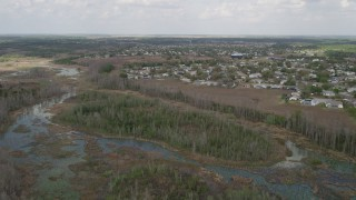 AX0035_083 - 5K stock footage aerial video of flying over swamps and residential neighborhoods, Clermont, Florida