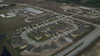 AX0035_086 - 5K stock footage aerial video fly over suburban homes toward an elementary school, Clermont, Florida