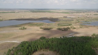 AX0035_088 - 5K stock footage aerial video of approaching small lakes and farmland, Clermont, Florida
