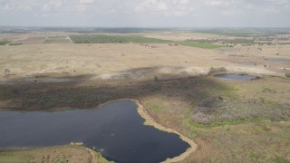 AX0035_089 - 5K stock footage aerial video of flying over a lake while approaching farmland, Clermont, Florida