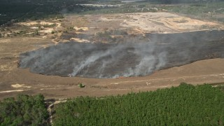 AX0035_095 - 5K stock footage aerial video of approaching a burn area and flames at a farm field, Winter Garden, Florida