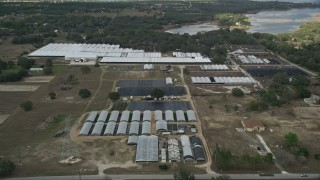 AX0035_096 - 5K stock footage aerial video approach greenhouses at a farm in Winter Garden, Florida