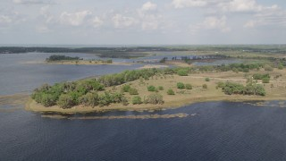 AX0035_101 - 5K stock footage aerial video fly over Johns Lake toward trees on the shore, Florida