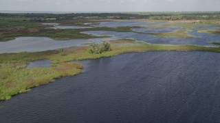 AX0035_103 - 5K stock footage aerial video fly over open water and patches of grassy land, Johns Lake, Florida
