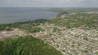 AX0035_109 - 5K stock footage aerial video fly over residential neighborhoods by lake shore, Winter Garden, Florida