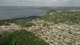 AX0035_109E - 5K stock footage aerial video fly over residential neighborhoods by lake shore, Winter Garden, Florida