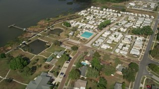 AX0035_111 - 5K stock footage aerial video approach mobile home park on the shore of a lake, Winter Garden, Florida