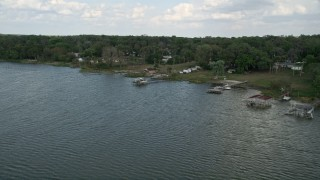 AX0035_129 - 5K stock footage aerial video approach docks and lakefront homes by Lake Apopka, Ocoee, Florida