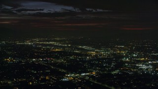 AX0156_002 - 8K stock footage aerial video passing suburban neighborhoods at night in Burbank, California