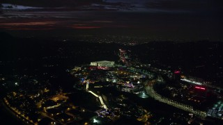 AX0156_005 - 8K stock footage aerial video of Universal Studios Hollywood in Universal City at night in California