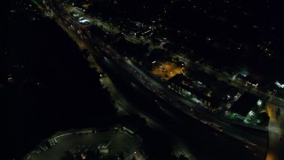 AX0156_006 - 8K stock footage aerial video of heavy traffic on Highway 101 through Studio City at night in California