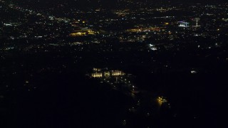 AX0156_011 - 8K stock footage aerial video orbiting the Griffith Observatory at night with a view of Hollywood in Los Angeles, California
