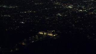 AX0156_012 - 8K stock footage aerial video orbiting the Griffith Observatory at night with a view of Hollywood in Los Angeles, California