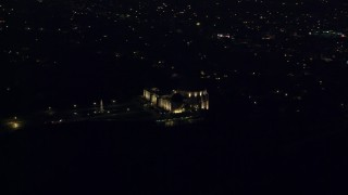 AX0156_013 - 8K stock footage aerial video of the hilltop Griffith Observatory at night with a view of Hollywood in Los Angeles, California