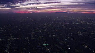 AX0156_032 - 8K stock footage aerial video flying over the city to approach Downtown Los Angeles skyscrapers at sunrise, California