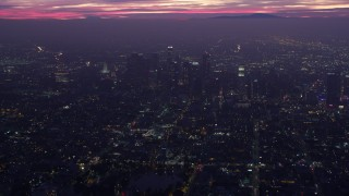 AX0156_033 - 8K stock footage aerial video approaching Downtown Los Angeles skyscrapers at sunrise, California