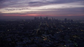 AX0156_042 - 8K stock footage aerial video flying across the city toward Downtown Los Angeles skyline at sunrise, California